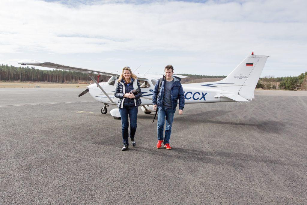 Christian Hieff und Manon Domizlaff stehen nach der Landung in Berlin vor dem Flugzeug